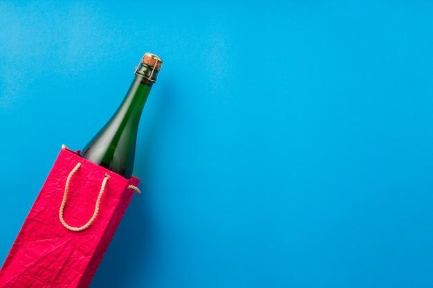Garrafa de champanhe em saco de papel vermelho brilhante na superfície azul Foto gratuita