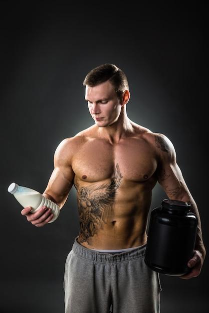 Garrafa de leite nas mãos de uma pessoa de esportes, homem saudável com o modo de vida adequado. tatuagem Foto Premium