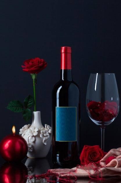 Garrafa de licor com cálice, vela e rosa em vaso Foto gratuita