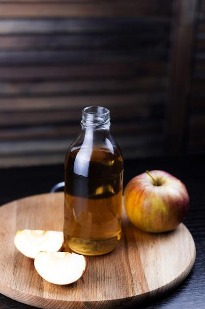 Garrafa de maçã fresca beber fundo de madeira Foto Premium