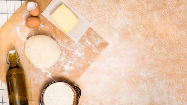Garrafa de óleo; farinha; bloco de manteiga; ovos e bola de massa no balcão da cozinha Foto gratuita