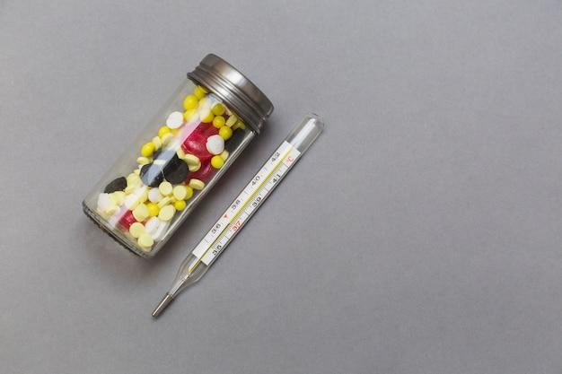 Garrafa de pílulas e termômetro no pano de fundo cinzento Foto gratuita