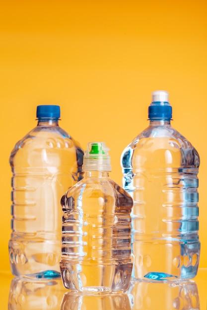 Garrafa de plástico de água mineral em um fundo amarelo brilhante Foto Premium