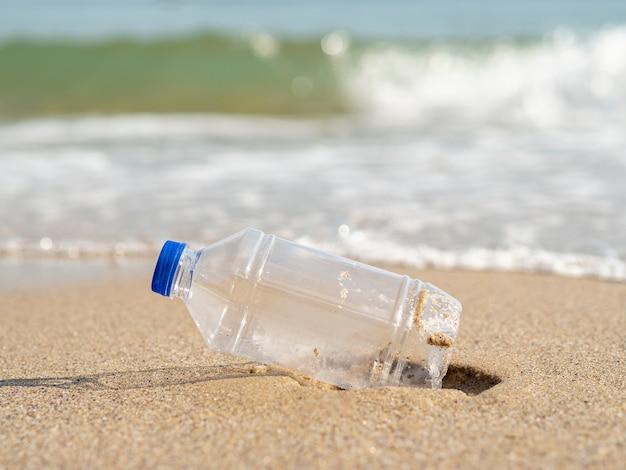 Garrafa de plástico deixada na praia Foto gratuita