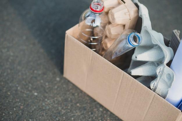 Garrafa de plástico e caixas de ovos na caixa de papelão de reciclar Foto gratuita