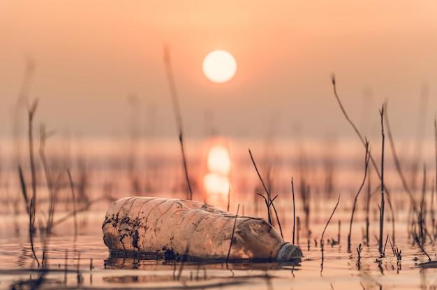 Garrafa de plástico no lago ao ar livre no dia quente de cozimento com manhã de nascer do sol Foto Premium