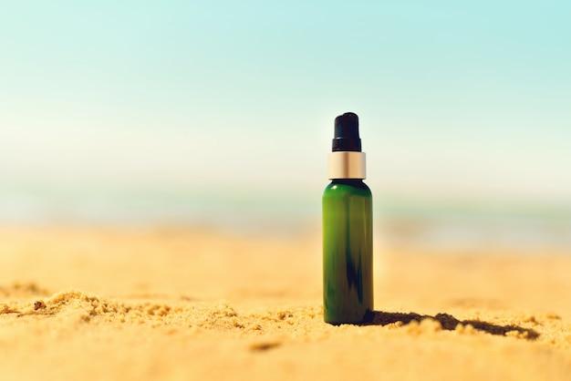 Garrafa de protetor solar na areia Foto Premium