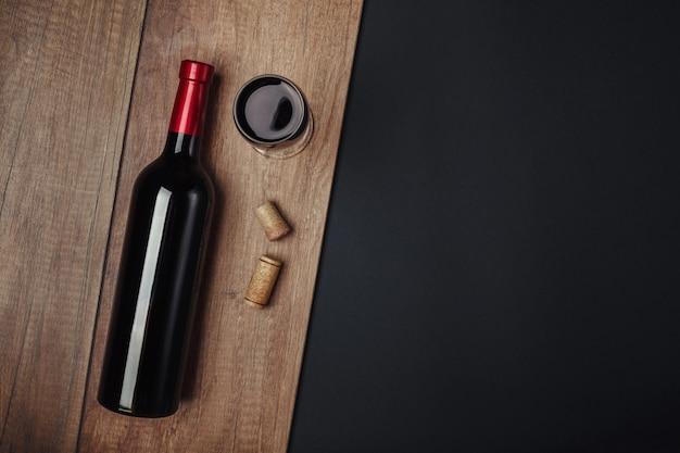 Garrafa de rolhas de vinho e um copo de vinho no fundo enferrujado Foto Premium