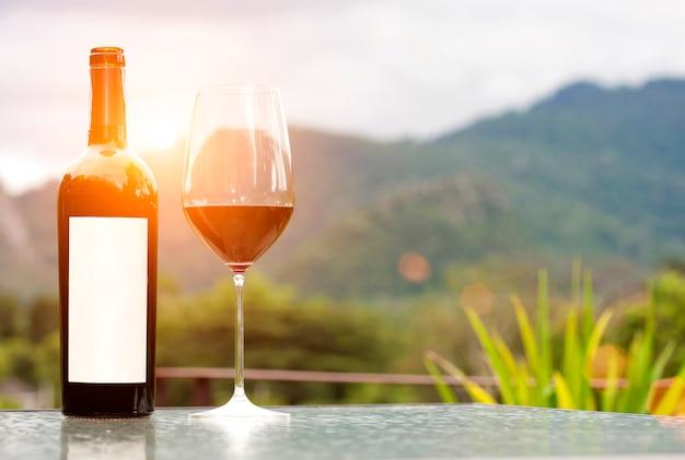Garrafa de rótulo em branco de vinho tinto com um copo na natureza Foto Premium