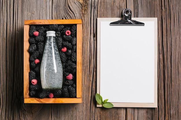 Garrafa de suco de amora na caixa de madeira com prancheta Foto gratuita
