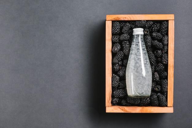 Garrafa de suco de amora na caixa de madeira Foto gratuita
