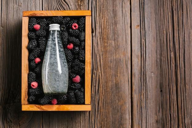 Garrafa de suco de amora preta sobre fundo de madeira Foto gratuita