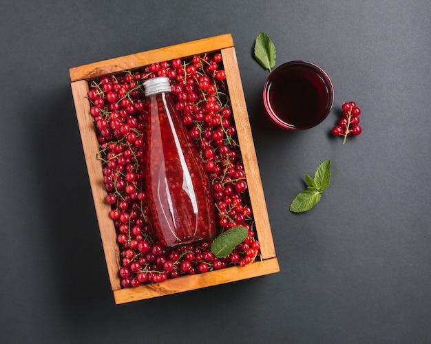 Garrafa de suco de cranberry vista superior em caixa de madeira Foto gratuita