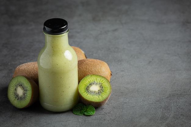 Garrafa de suco de kiwi colocada no chão escuro Foto gratuita