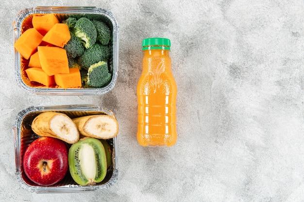 Garrafa de suco de laranja com frutas e legumes em caçarolas Foto gratuita
