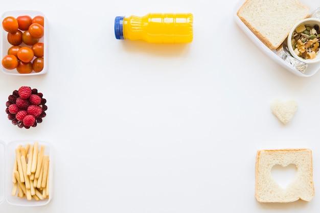 Garrafa de suco perto de comida saudável Foto gratuita