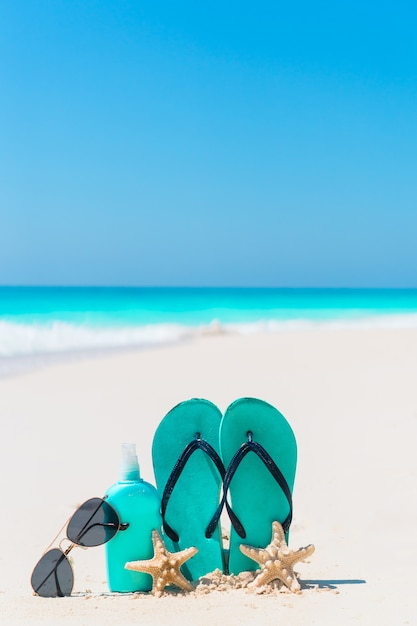 Garrafa de suncream, chinelos, estrela do mar e óculos de sol na praia de areia branca com vista para o mar Foto Premium