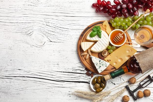 Garrafa de vinho branca, uva, mel, queijo e copo de vinho sobre fundo branco de madeira Foto Premium