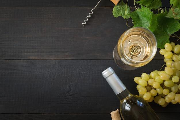 Garrafa de vinho branco com um copo de vinho, uvas maduras na mesa de madeira preta. Foto Premium
