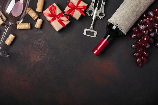Garrafa de vinho, caixa de presente, uvas vermelhas, saca-rolhas e rolhas, em fundo enferrujado Foto Premium