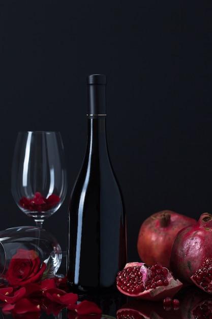 Garrafa de vinho com romãs, taças e pétalas de rosa Foto gratuita