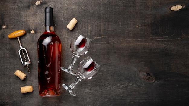 Garrafa de vinho de vista superior com copos e saca-rolhas ao lado Foto gratuita