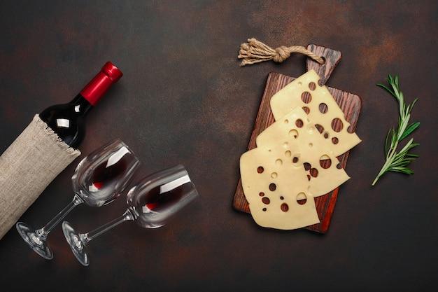 Garrafa de vinho, dois copos e queijo maasdam fatiado em uma placa de corte no fundo enferrujado Foto Premium