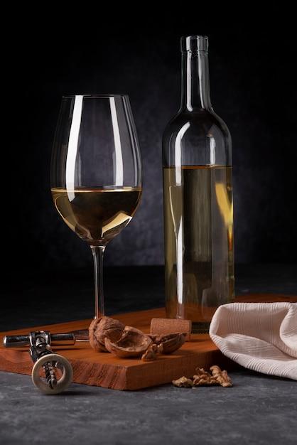 Garrafa de vinho e copo com abridor Foto gratuita