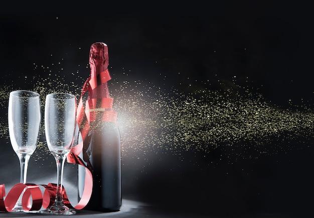 Garrafa de vinho e copos com fita vermelha e brilhos dourados Foto Premium