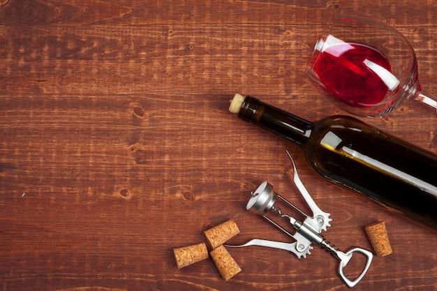Garrafa de vinho e cortiça e saca-rolhas na mesa de madeira Foto Premium