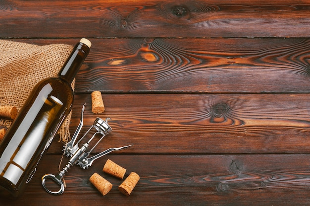 Garrafa de vinho e cortiça e saca-rolhas no fundo da mesa de madeira Foto Premium