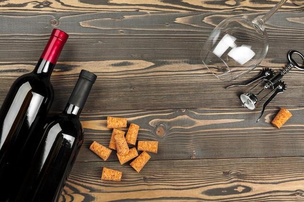 Garrafa de vinho e rolha e saca-rolhas na mesa de madeira Foto Premium