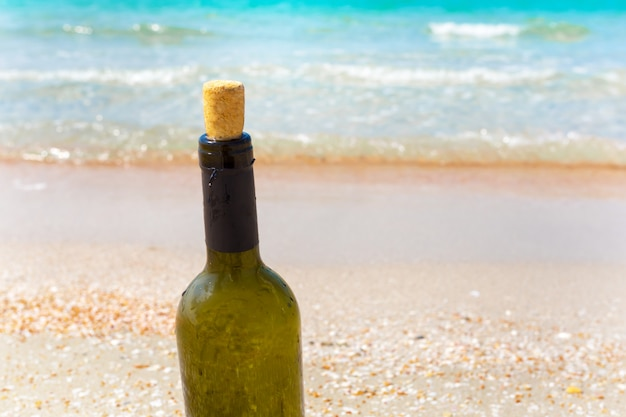 Garrafa de vinho na areia na praia Foto Premium