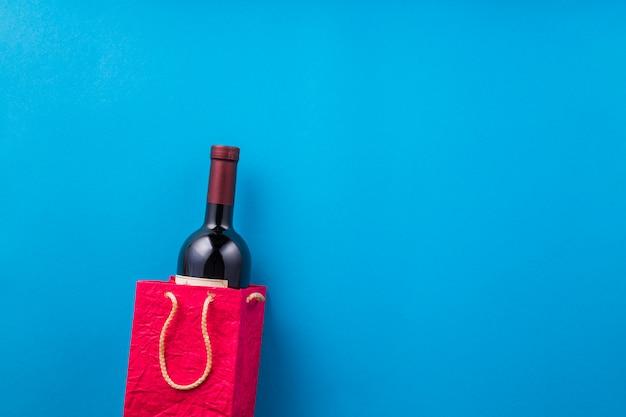 Garrafa de vinho nova no saco de papel vermelho contra o pano de fundo azul Foto gratuita