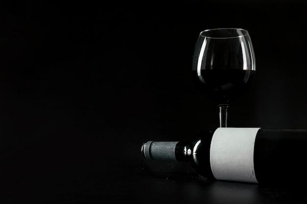 Garrafa de vinho perto do copo Foto gratuita