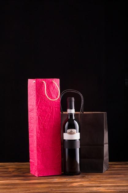 Garrafa de vinho preta com saco de papel bonito sobre a mesa de madeira Foto gratuita