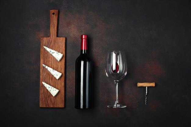 Garrafa de vinho, queijo stinky azul, saca-rolhas e um copo de vinho no fundo enferrujado Foto Premium
