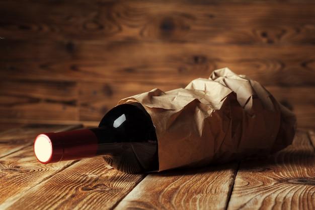 Garrafa de vinho sobre a parede de madeira Foto Premium