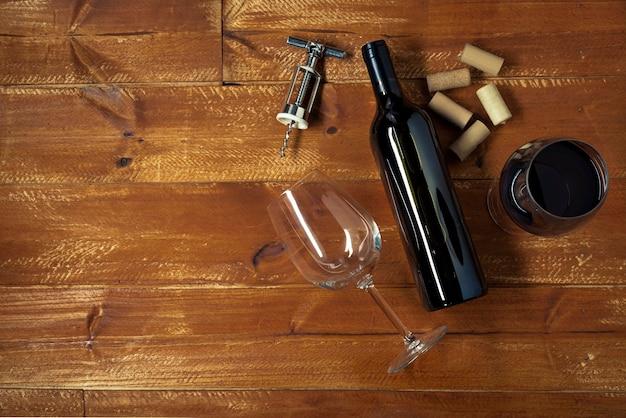 Garrafa de vinho tinto e copos com saca-rolhas Foto gratuita