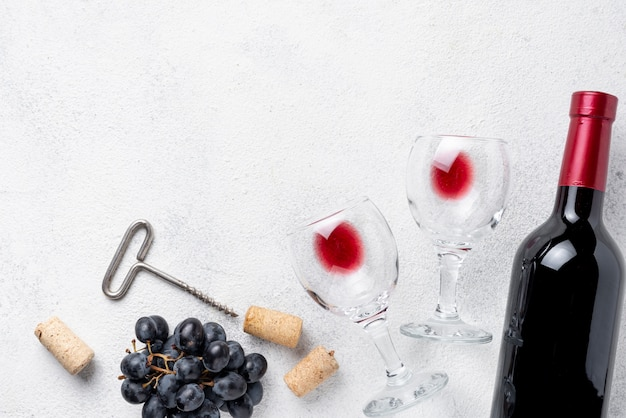 Garrafa de vinho tinto e copos na mesa Foto Premium
