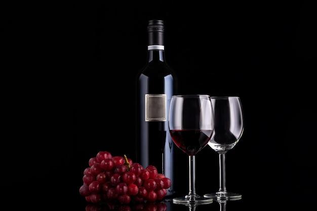 Garrafa de vinho tinto fechada com rótulo vazio, pequeno ramo de uva e dois copos em fundo preto com reflexões Foto Premium