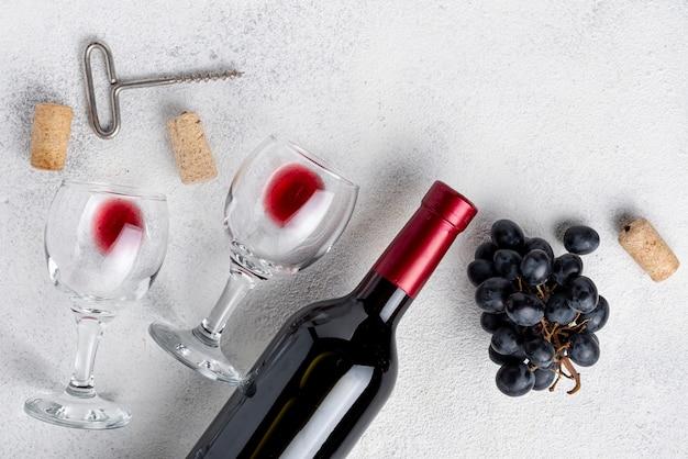 Garrafa de vinho tinto plana leigos na mesa Foto gratuita