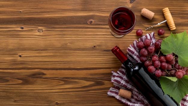 Garrafa de vinho vista superior com vidro em fundo de madeira Foto gratuita