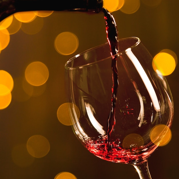 Garrafa derramando vinho tinto em vidro com efeito bokeh Foto Premium