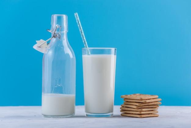Garrafa do leite fresco com palha e cookies no fundo azul. minimalismo colorido. produtos lácteos saudáveis com cálcio Foto Premium