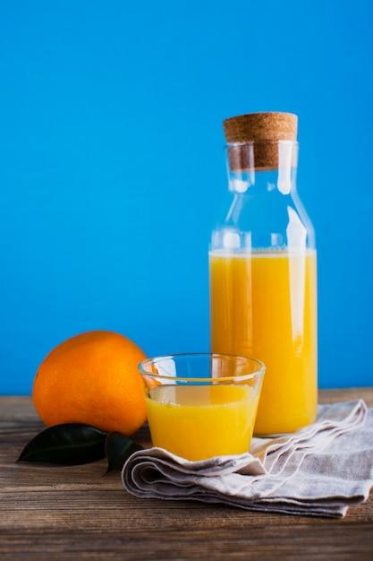 Garrafa e copo de suco de laranja de vista frontal Foto gratuita
