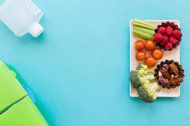 Garrafa e lancheira perto de comida saudável Foto gratuita