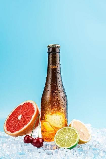 Garrafa fechada de cerveja de vidro marrom no gelo. frutas ficam nas proximidades. conceito de cerveja artesanal de frutas ou cidra Foto Premium