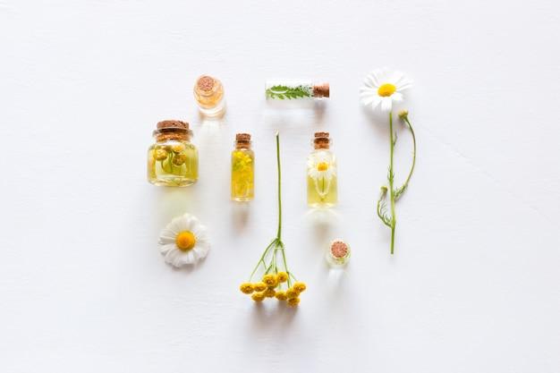Garrafas com cosméticos naturais para cuidados com o rosto e corpo e flores silvestres em branco Foto Premium