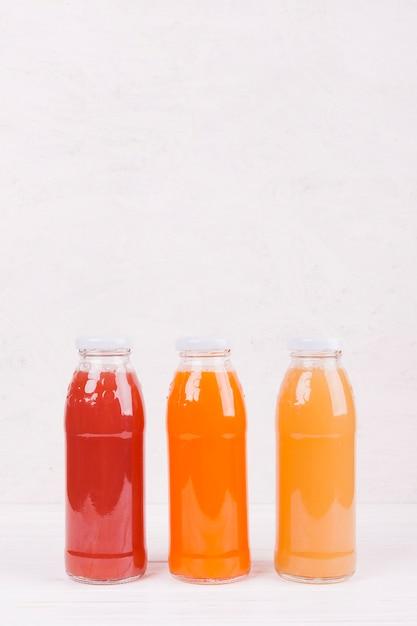 Garrafas com suco de frutas coloridas Foto gratuita